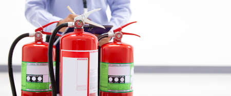 Fire engineering checking pressure gauge level of fire extinguishers tank in the building concepts of protection and prevent for emergency and safety rescue and fire training.