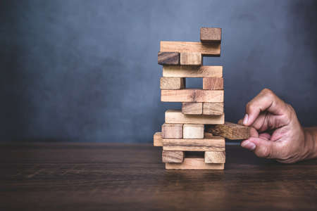 Close-up hand pull wooden block from other the wood block stacked in tower shape concepts of financial risk management and strategic planning. Reklamní fotografie