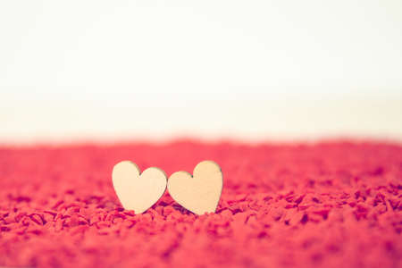 Close-up two hearts for love symbol on a red sand background. Concept the day of love 14 February happy valentine's day.