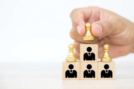 Hand choose chess on wooden toy blocks stacked in a pyramid with people icon concepts of human resources for business team organizations and leadership. Reklamní fotografie