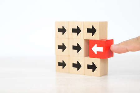 Close-up hand choose cube wooden toy block stacked with arrow icon pointing to opposite directions for way of business change leader planning company and transform concept.