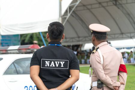Men in the form of Thai Navy security personnel stand ready