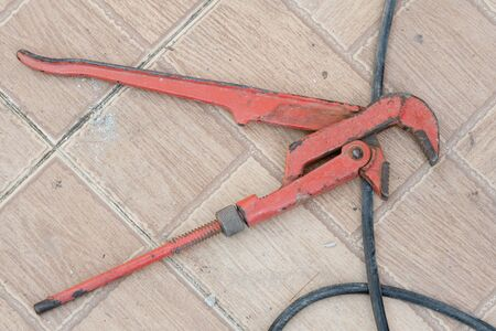 old rusty red pipe wrench on concrete floor Foto de archivo