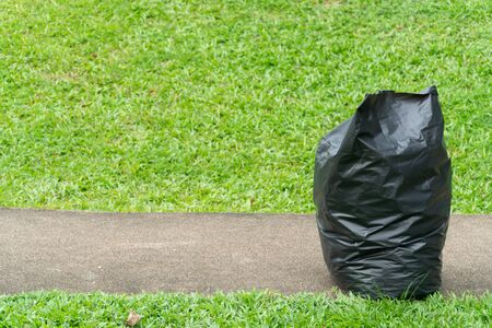 Black garbage bags on the Green grass in a park Banco de Imagens