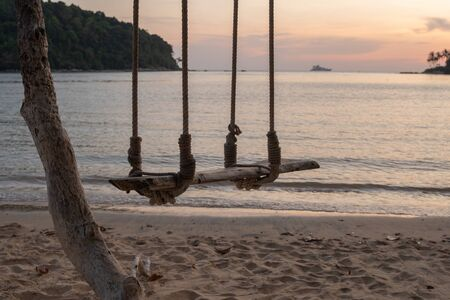 evening sun shining Sea wave on the sunset beach and Wooden swing hang under a tree