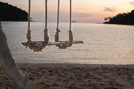 Wooden swing hang under a tree sand and sea beach on the background