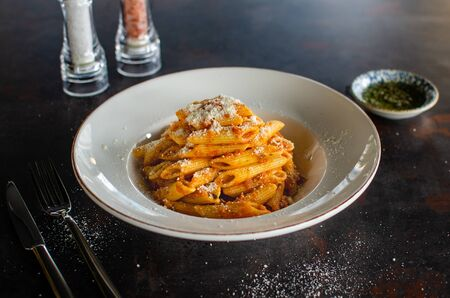 Italian pasta. Penne pasta with with parmesan cheese in white plate on metallic background. Dinner. Lauch. Top view. Slow food concept stock photo Banco de Imagens