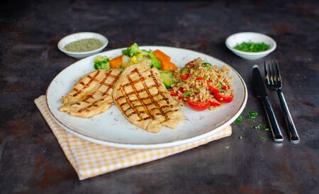 Grilled chicken fillet with boiled fresh vegetables and rises, rustic metallic background.Top view with copy space.