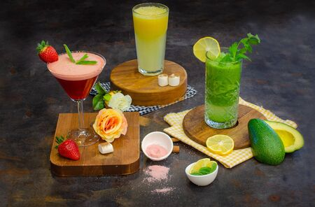 Healty smoothies and juices with wooden plate on metallic background - perspective view