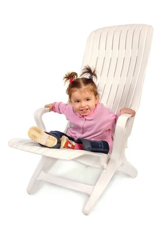 Small girl sitting on a chaise longue and smiling Stock Photo - 2334839