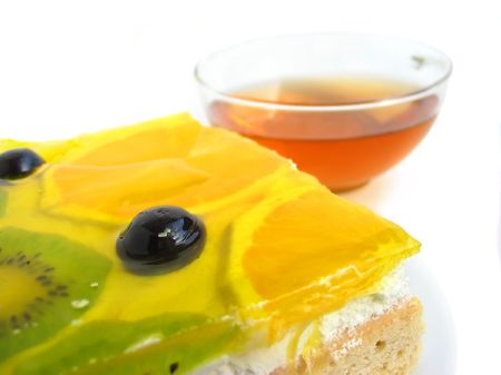 Delicious tart covered with fresh glazed fruits with tea photo