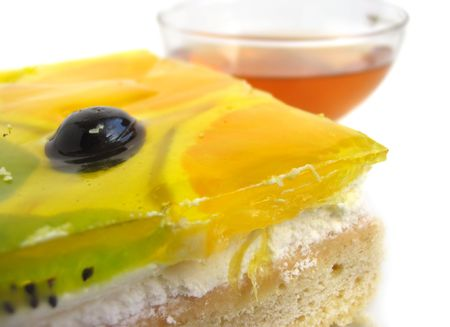 Delicious tart covered with fresh glazed fruits with tea cup photo