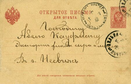 Vintage Russian Empire postcard from early 1900s with cancelled stamp, Russian Empire state emblem and written note with address. Russian Empire photo