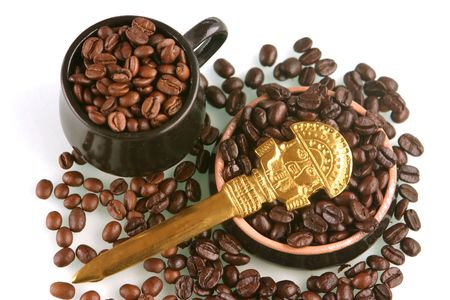 Coffee beans of two kind in a little brown cup and saucer with gold ritual knife from Peru photo