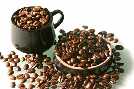 Coffee beans of two kind in a little brown cup and saucer on a white background photo