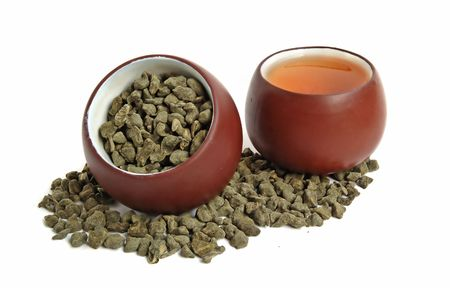 Cup of dried green tea leaves with ginseng and cup of tea photo
