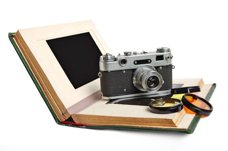 Old photo album with empty pictures and vintage camera with photofilters photo