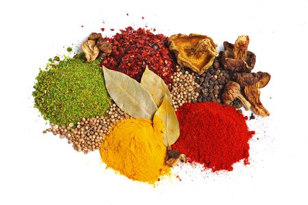 colored powder: Piles of spices: parsley, red paprika, whole black pepper, white coriander, curcuma, laurel leaves and dry porcini mushrooms.