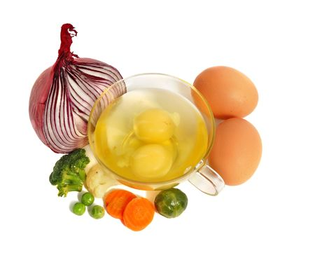 Raw eggs in a glass cup and different vegetables, healthy breakfast. photo