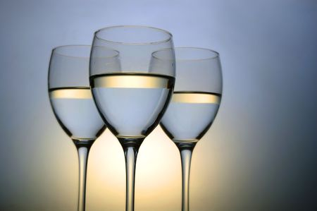 Three wine glasses on color background