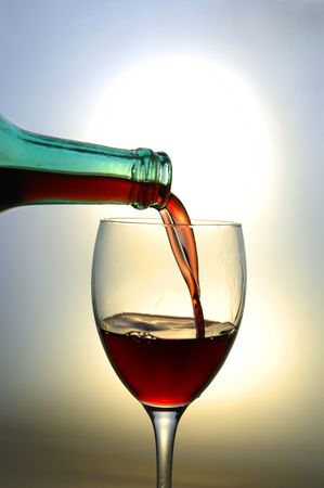 Red wine pouring into a wine glass against the setting sun background photo