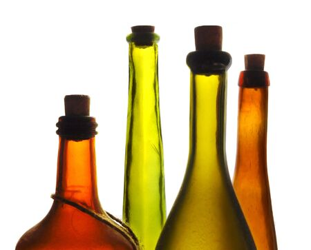 Old multicolored wine bottles isolated on white photo