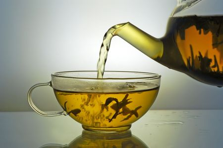 brew: Green tea pouring into glass cup from teapot on blue background