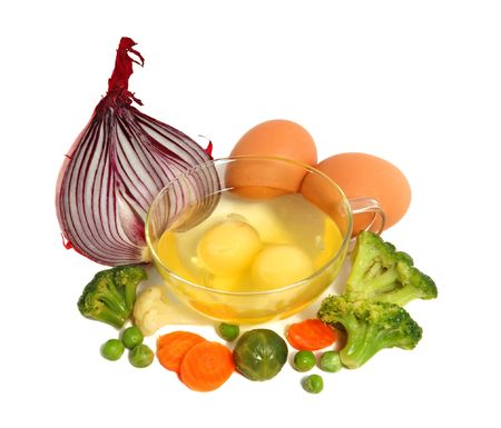 pungent: Raw eggs in a glass cup and different vegetables, healthy breakfast.
