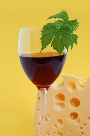 Glass of red wine with grape leaves and piece of cheese on yellow background photo