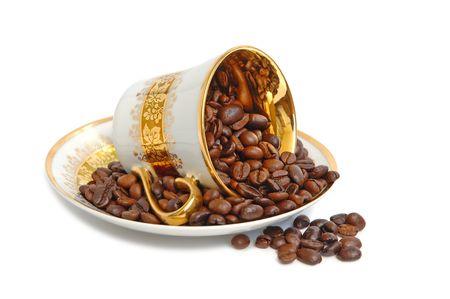 overturn: Tazza di caff� capovolgimento d'oro con i chicchi di caff� Archivio Fotografico