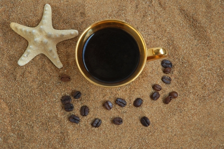Gold cup with coffee, beans and starfish on a sea beach photo