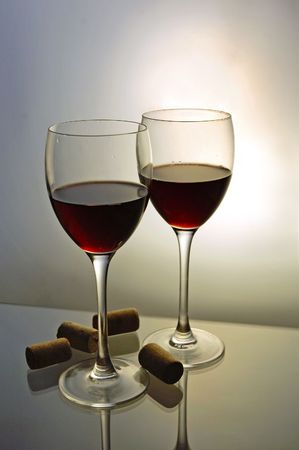 Two glasses with red wine with bottle corks photo
