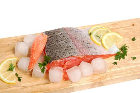 Raw salmon fillet on a wooden cutting board photo