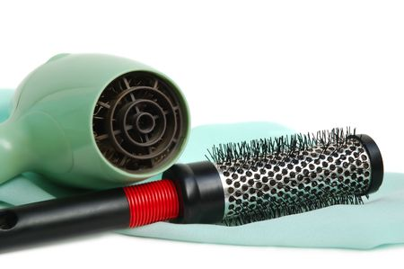 The hair dryer and hairbrush on a satin  photo