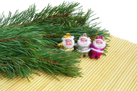 pine three: Three Santas sitting on  bamboo mat and a pine tree Stock Photo