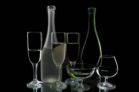Wine bottles and glasses against a black background photo