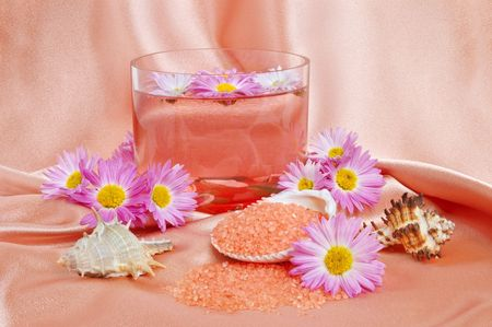 A bright pink spa and body care background. Salt and flower floating in glass bowl. photo