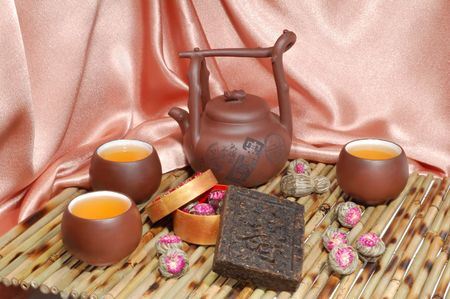 Chinese teapot and cups with aromatic flower tea and black pu-erh tea from yunnan province in China. Leaves undergoes double fermentation and compressed into bricks. Healthy drink. photo