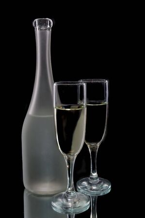 Pair of wine flutes and wine bottle against a black background Stock Photo - 4149919