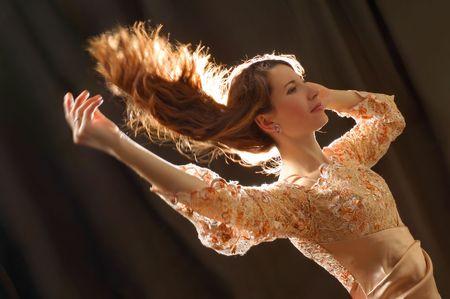 Beautiful woman dancing with hair flying photo
