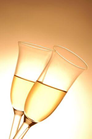 Pair of champagne flutes on orange background photo