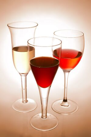 Various wine glasses on pink background photo