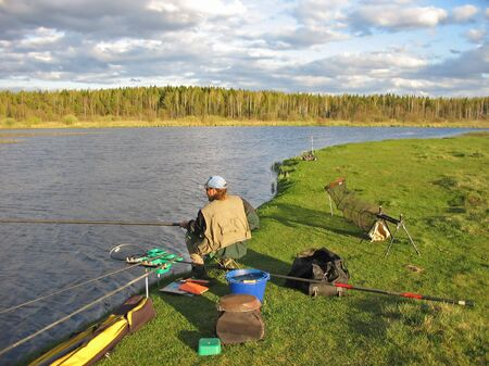 Seated men fishing off a shoreline Stock Photo - 4324734