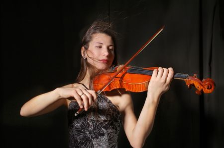 bowing: Beautiful violinist musician playing on black