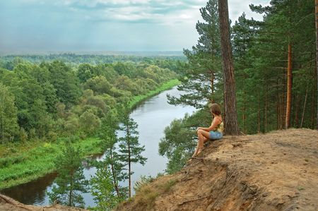 lone pine: Young woman sitting and meditate on steep with peaceful river view Stock Photo