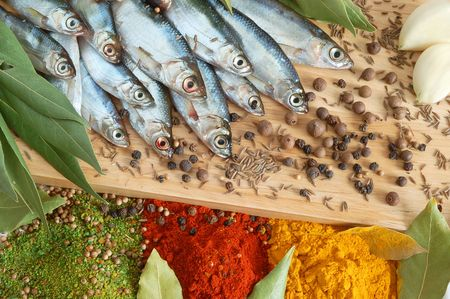 caraway: Fish with fresh bay leaves, garlic, black pepper, parsley, oregano, red paprika, curcuma and caraway seeds on wooden cutting board
