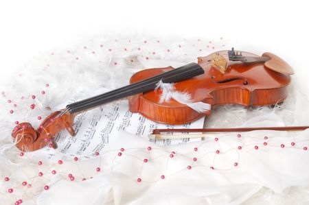 Violin and notes on white silk background with boa and furs photo