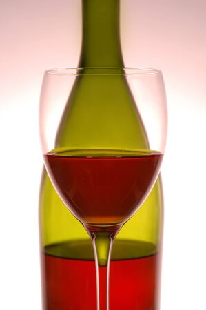 Red wine and green bottle on pink background photo