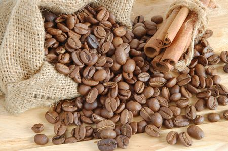 spilling: Coffee beans and cinnamon sticks in canvas sack on wooden background