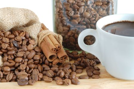Coffee beans and cinnamon sticks in canvas sack on wooden background photo